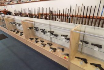 Display cases for pistols and display racks for rifles at a gunsmith shop in Billerica, MA